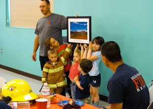 Interim Fire Chief, Tim Darland, presents outgoing Chief Doug Hutchison a commemorative photo, with lots of enthusiastic help. Photo: Gwen Berry